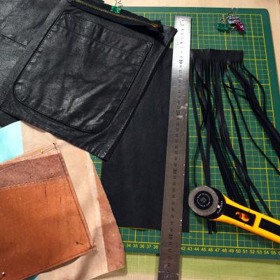 Ett pysselbord med läderbitar som skurits ur en gammal skinnjacka, en linjal av metall och en rullkniv.