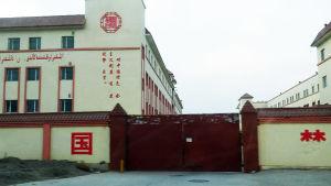 En stängd port till ett stort område med höga byggnader.