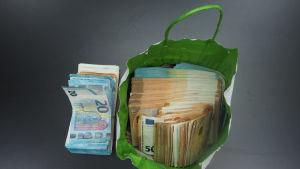 En papperskass med en stor bunt 50-eurossedlar. Bredvid kassen en annan bunt sedlar. Polisen beslagtog dessa 60 000 euro från en av de misstänkta på Helsingfors-Vanda flygfält. Enligt förundersökningen skulle den misstänkta föra pengarna till Spanien.