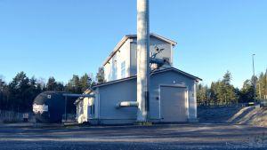 Kimitoöns värmes flisanläggning i Dalsbruk. En liten industrihall med lång skorsten.
