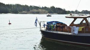En trämotorbåt fast i bojen i en gästhamn med kläder hängande på tork runt relingen. Solen skiner och i bakgrunden kör en mindre, öppen motorbåt.