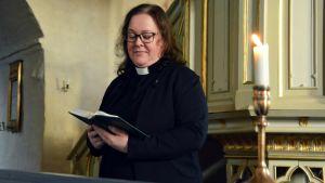 Prästen Janette Lagerroos i en kyrka med en bibel i handen.