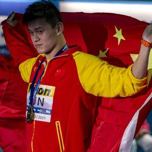 Sun Yang håller upp den kinesiska flaggan bakom sig.
