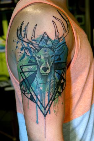 En gemoetrisk tatuering av en hjort med stänk av vattenfärg.