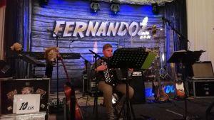 en ung pojke sitter på scen och spelar dragspel. Bakom honom en stor  text där det står Fernandoz (ett svenskt dansband).