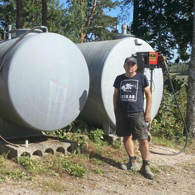 Karl Åberg står vid några bränsletankar som finns på hans gård i Ingå.