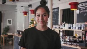 Porträtt på ung kvinna med mörkt hår i tofs på huvudet och svart t-shirt. I bakgrunden kafémiljö.