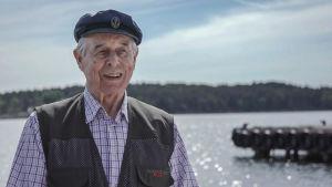 Vanhempi herrasmies kalastusliivissä ja tummansinisessä kipparihatussa.