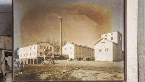 Mustavalkoinen kuva: vaaleita tiilisiä tehdasrakennuksia, yksi tehdaspiippu, edustalla useampi 1950-luvun auto.