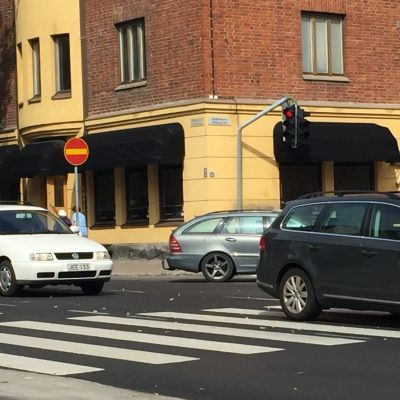 Tre personbilar som kör i en korsning.