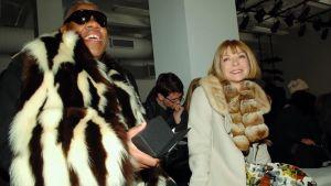 André Leon Talley ja Anna Wintour hymyilevät turkit päällä jossain muotitapahtumassa. Kuva dokumenttielokuvasta.