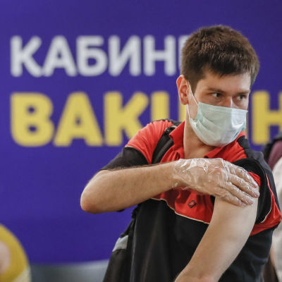 En ung man har fått coronavaccin i shoppingcenter i Moskva.