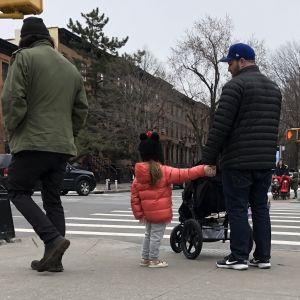 Flicka håller pappa i handen, väntar på grönt ljus