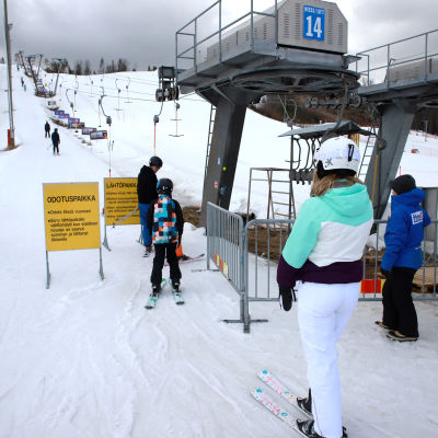 Laskettelijoita menossa hiihtohissiin.