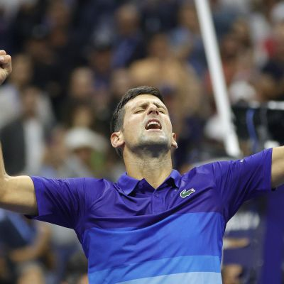 Novak Djokovic sträcker armarna i luften.