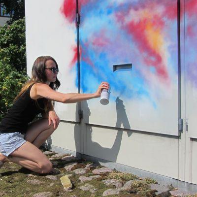 Nainen tekee graffitia sähkökaappiin