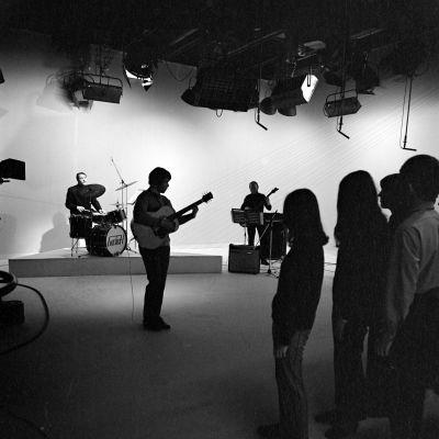 """Yleisradion televisio-ohjelma """"Popmessu. Pop-messu"""". Reijo Kariskoski (rummut), Timo Ruottinen (kitara), Lauri Ala-Anttila (basso) ja 17 henkinen seurakuntanuorista koottu kuoro."""