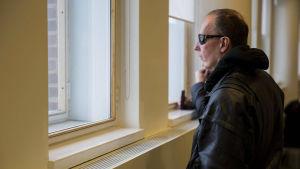 Michael Penttilä i solglasögon och mörk rock inomhus