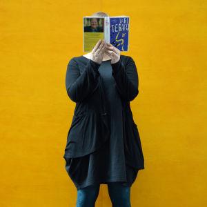 Nainen lukee Jari Tervon kirjaa, kirja peittää kasvot