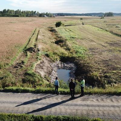 Bottendammar vid ett dike, en bäck som leder till en å. Bild tagen med drönare uppifrån. Man ser också tre personer som står nära en konstgjord damm.