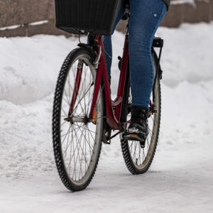 Lähikuva pyörästä jossa pyöräilijä polkee talvisessa Oulussa