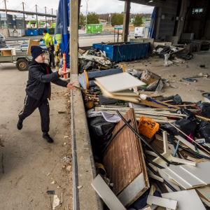 Nuori mies heittää lastulevyjä pois kaatopaikalle