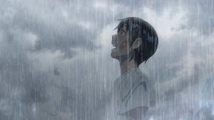 Pojken Hodaka står i ett grått regn och ser skrattande upp mot himlen.