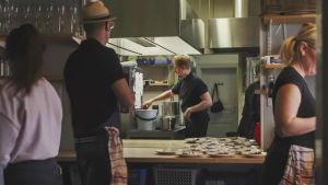 Restaurangkök, kock rör om i gryta, i förgrunden färdiga portioner på bord.