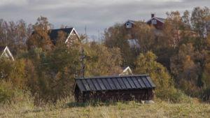 Mycket lågt, litet trähus med ortodoxt kors på taket.