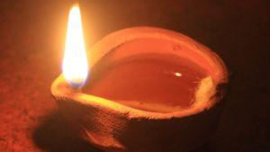 Närbild av en indisk oljelampa gjord av lera. Varmt, orange-färgat sken på bilden.