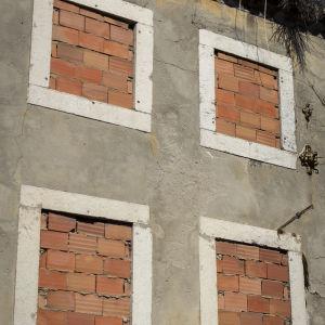 Ett gammalt hus med igenmurade fönsterluckor.