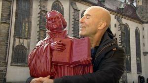 Mark Levengood med en röd Martin Luther-staty i famnen