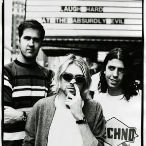 Nirvana poserar. Kurt petar sig i näsan.