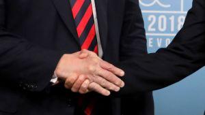 Närbild av två högerhänder. 29 sekunder räckte den starka handtryckningen mellan Trump och Macron.