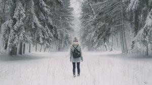 Tyttö kävelee metsätiellä johon on satanut ensilumi.