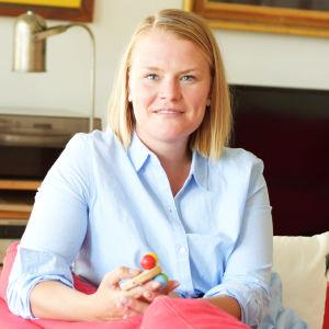Lena Sommer sitter i en röd soffa och har en barnleksak i handen.