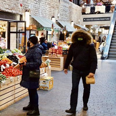 Grönsaksförsäljning på inomhusmarknaden Balti Jaama Turg i Tallinn. De fyra personerna på bilden använder munskydd på olika sätt - från inget till munskydd och jackans huva tätt dragna över ansiktet.