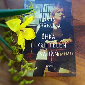 Anja Erämajan runoteos kukkamaljakon vieressä