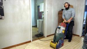 En skäggig man slipar ett golv.