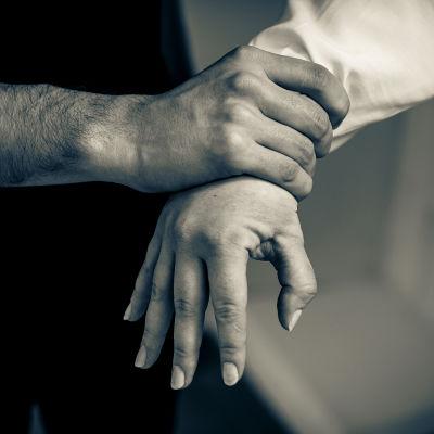 Miehen käsi puristaa naisen kättä.