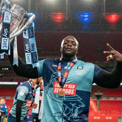 Adebayo Akinfenwa poserar med League One-pokalen i ena handen.