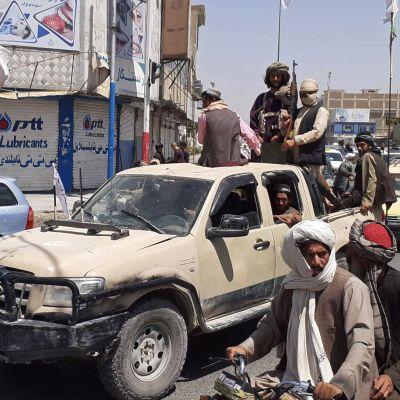 Taliban -taistelijat ajavat autolla.