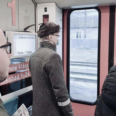 Passagerare på tåget mellan Tartu och Tallinn har ställt sig vid tågets dörr för att köa för avstigning.