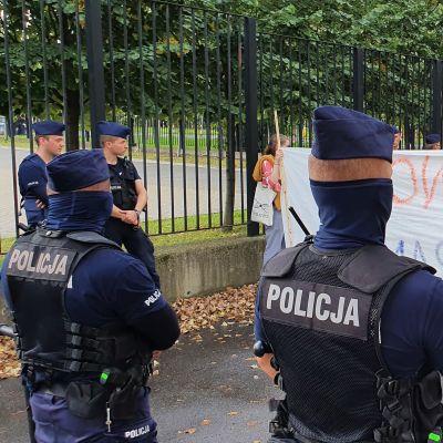 Delvis maskerade polska polismän övervakar en fredlig flyktingvänlig demonstration utanför Polens inrikesministerium.