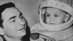 Kosmonautti pitelee lasta, jolla on päässään kosmonautin kypärä.