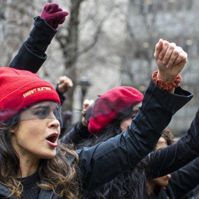 Kvinnor i röda hattar och svarta kläder står på rad med händerna i luften och ropar.