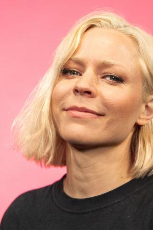 Vesala hymyilee kasvokuvassa vienosti kameralle pinkin seinän edessä.