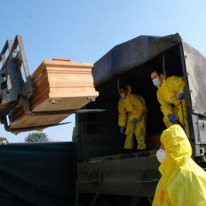En kista lastas in i en militärlastbil i Bergamo