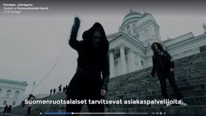Skärmdump från Finsk ungdoms video med en person och en piska på domkyrkans trappa i Helsingfors.