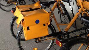 Bakdelar av postcyklar, orange västka med Itellas logo.